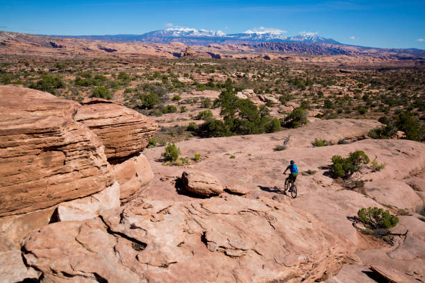 een man rijdt zijn mountainbike over een langlaufloipe in moab, utah, usa op een zonnige dag. - moab utah stockfoto's en -beelden