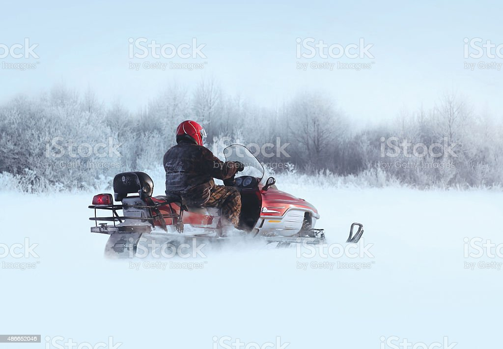 Man rides snowmobile through snowdrifts in winter day stock photo