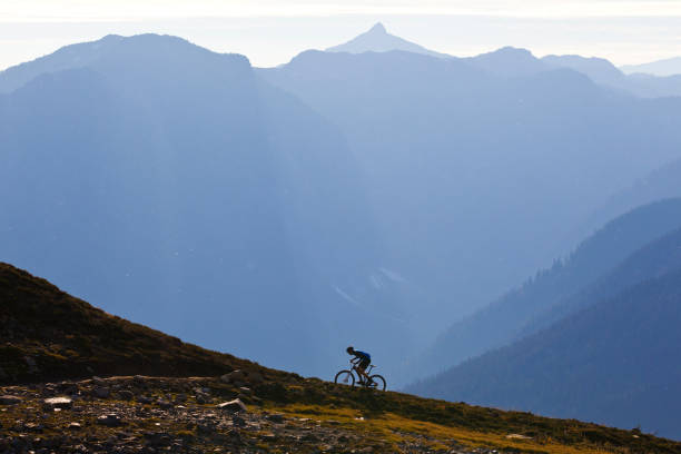 A man rides up a steep mountain bike trail in British Columbia, Canada. stock photo