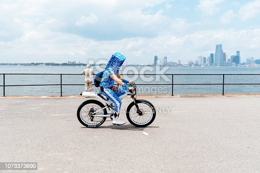 New York City, USA - June 24, 2018: Man riding a bicycle along promenade in Governors Island wearing a cardboard box on his head against skyline