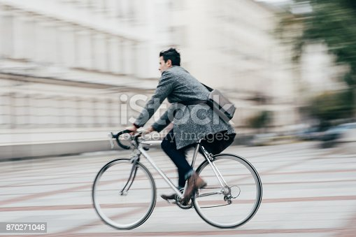 Elegant man riding a bicycle in the city.