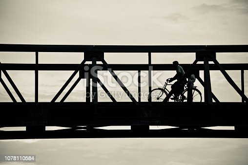 A man riding a bicycle on a metallic bridge way