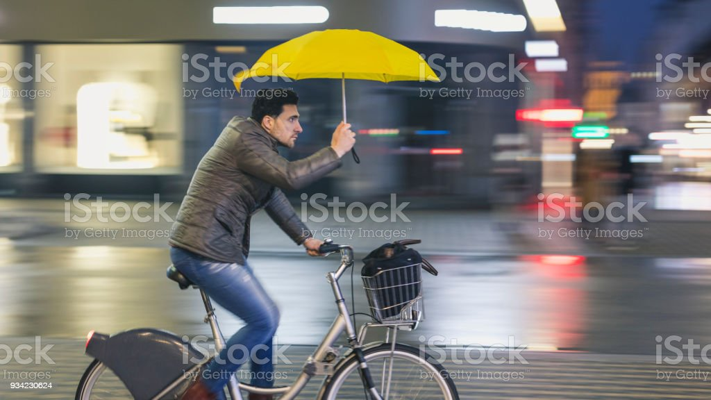 Young man riding a bicycle and holding an umbrella in the city on a...