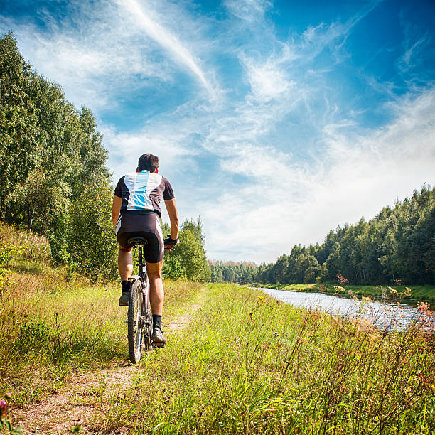 Man Riding a Bicycle on River Bank. Summer Photo. – Foto