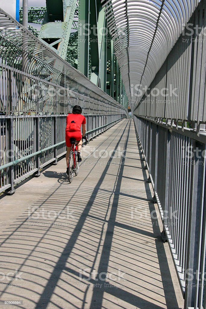 Man riding a bicycle on the Montreal Jacques Cartier bridge stock photo