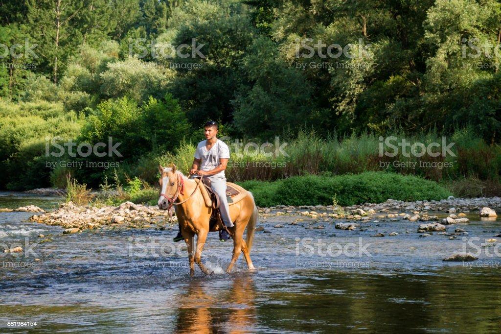 Hombre a caballo a través de un arroyo en Italia - foto de stock