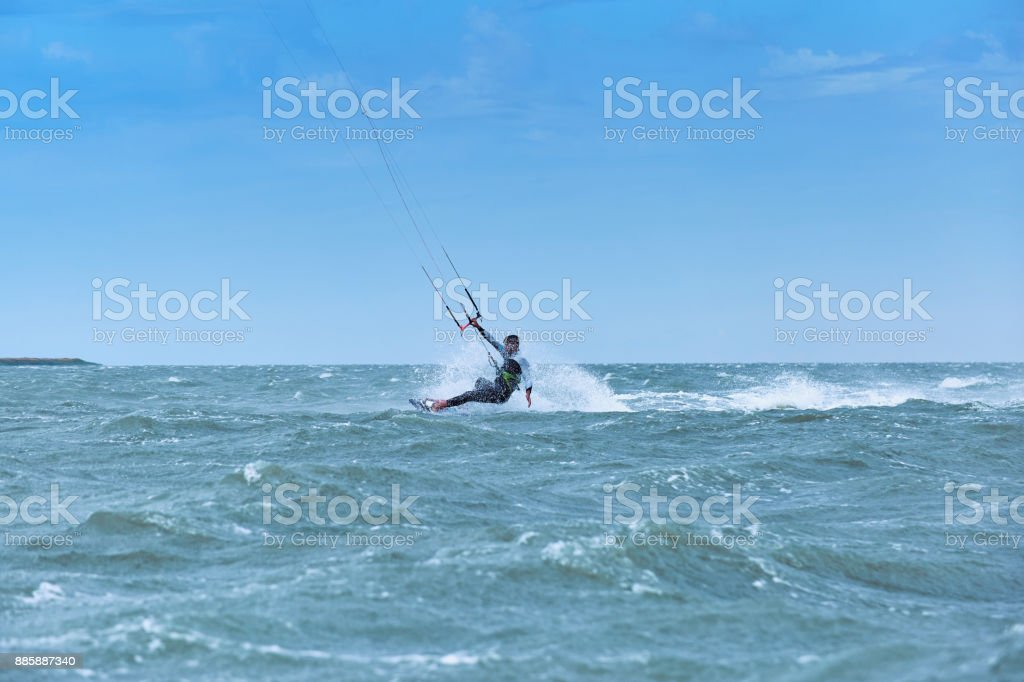Man riding a kite surfing on the waves in the summer. stock photo