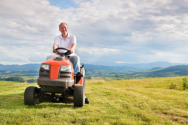 man riding a lawn tractor - riding lawn mower stock photos and pictures