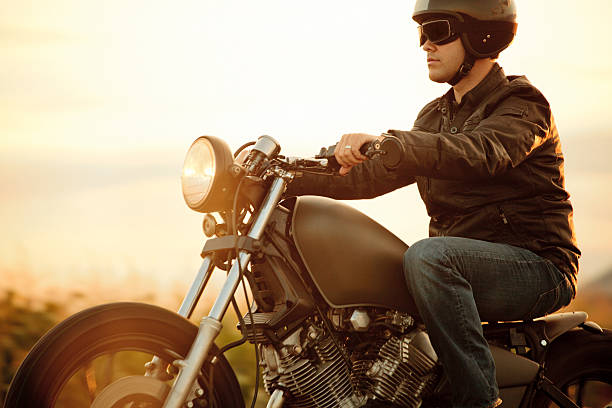 a man riding a motorcycle in the sunset - biker stock photos and pictures