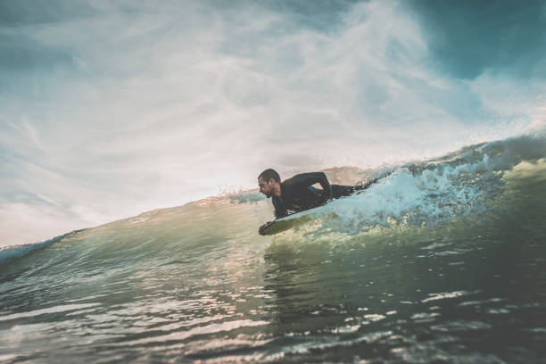 Man riding a wave on his bodyboard stock photo