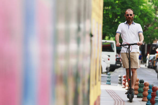 man riding an electric scooter - electric push scooter stock photos and pictures