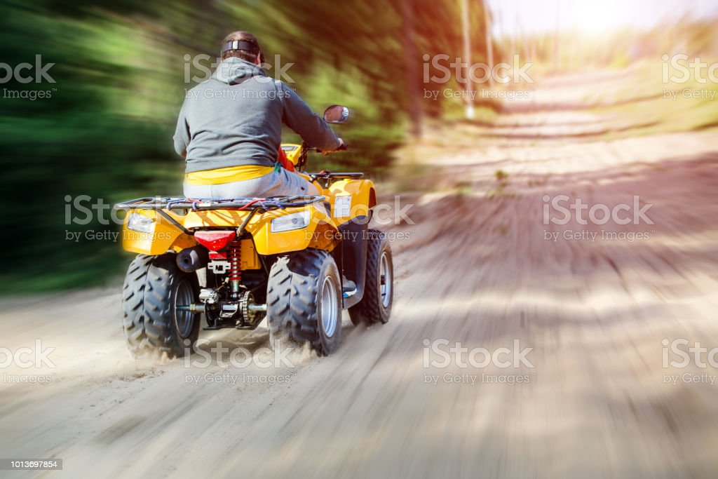 A man riding ATV on a sand road, back view stock photo