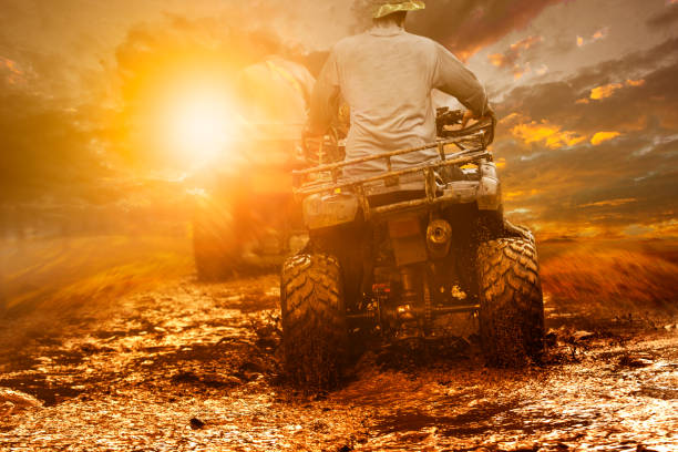 man riding atv through mud terrain field man riding atv through mud terrain field quadbike stock pictures, royalty-free photos & images