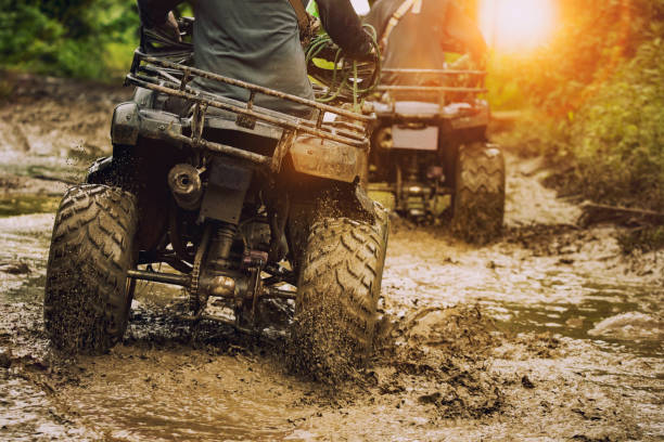 man riding atv vehicle on off road track ,people outdoor sport activitiies theme - bike tire tracks foto e immagini stock