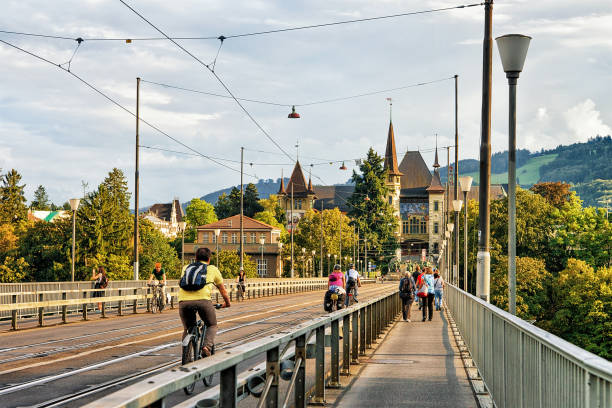 Man riding bicycle and other people on Kirchenfeld bridge and Historical Museum building on the background, Brn-Mittelland district, Switzerland. stock photo