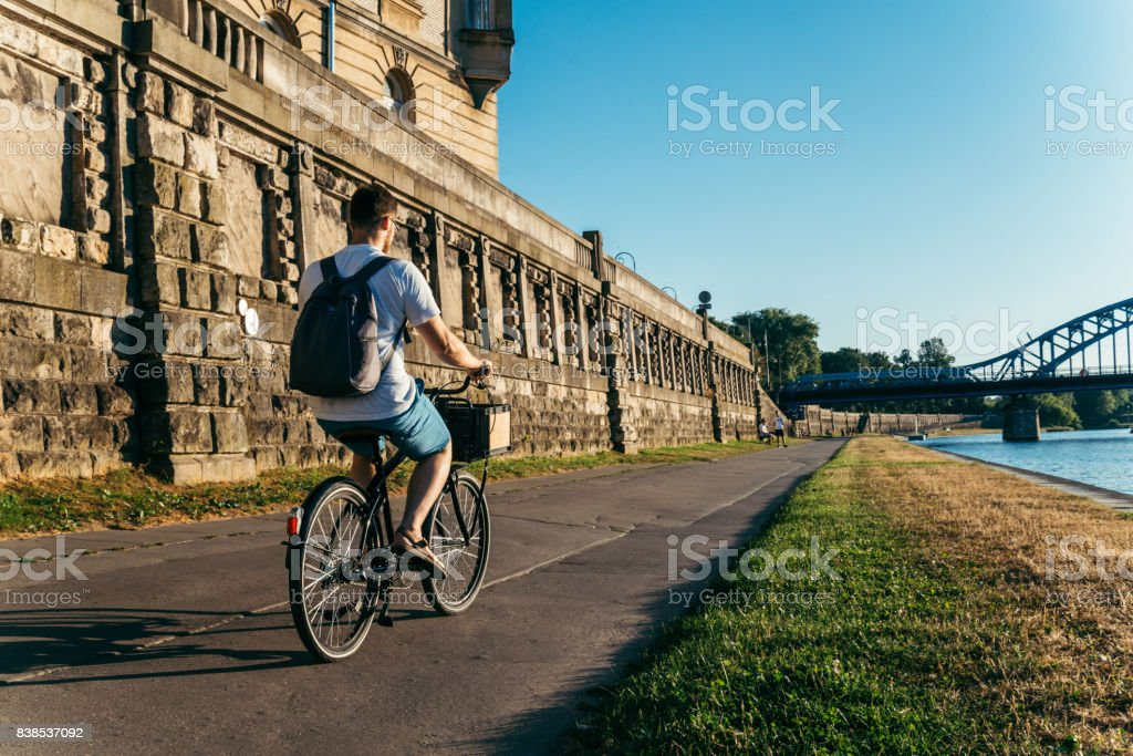 man riding bicycle at embankment at the sunset stock photo