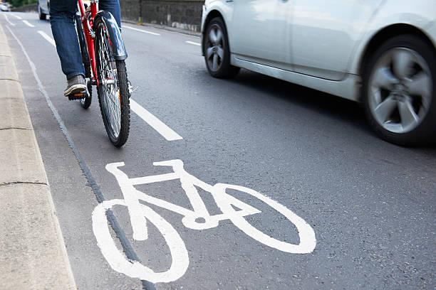 mann auf fahrrad in cycle lane - fahrradwege stock-fotos und bilder