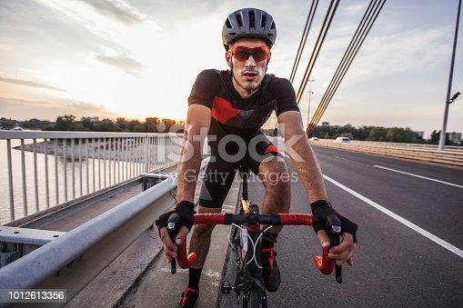 istock Man riding bicycle on the bridge 1012613356