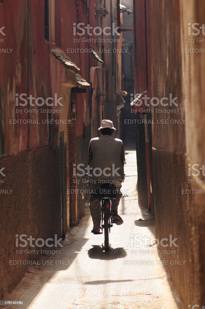 Man riding Bicycle. Red old narrow street. Marrakesh, Morocco. stock photo