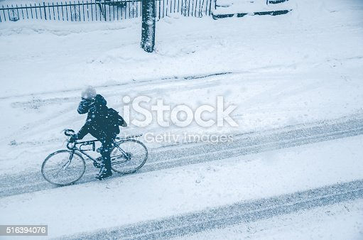 istock Man riding bike during snow storm 516394076