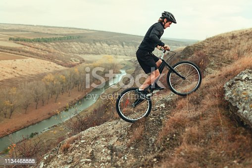 Side view of male in helmet and sportswear riding up rough hill near beautiful river in countryside