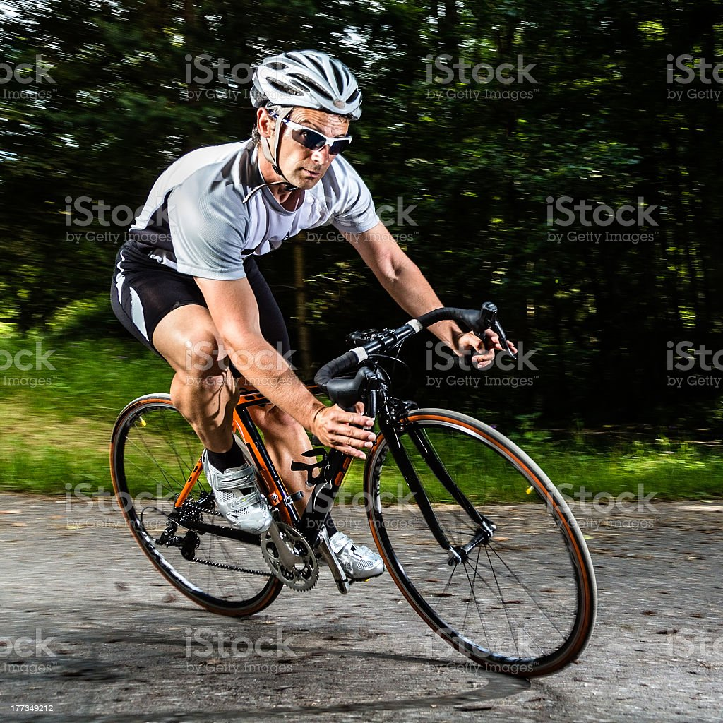 Man riding black and orange racing bike stock photo