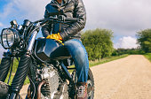 Unrecognizable young man riding a custom motorbike outdoors