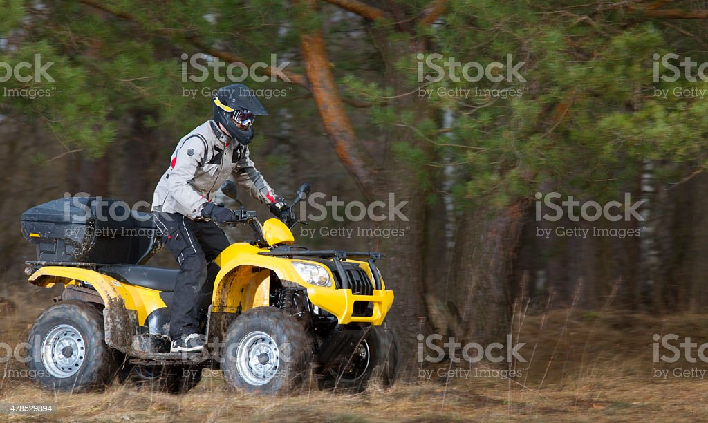 Man riding dirty 4x4 ATV quad bike stock photo