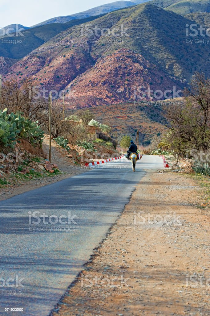 Man riding donkey Atlas mountains stock photo