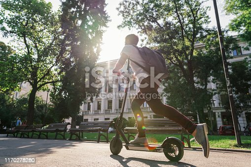 Side view image of young man riding electric scooter downtown