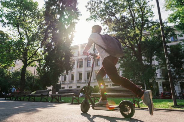 man riding e-scooter through the city park - electric push scooter stock photos and pictures