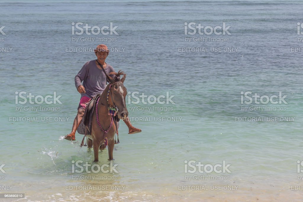 A man riding his horse in the shallow blue and green tropical  water - Royalty-free Activity Stock Photo