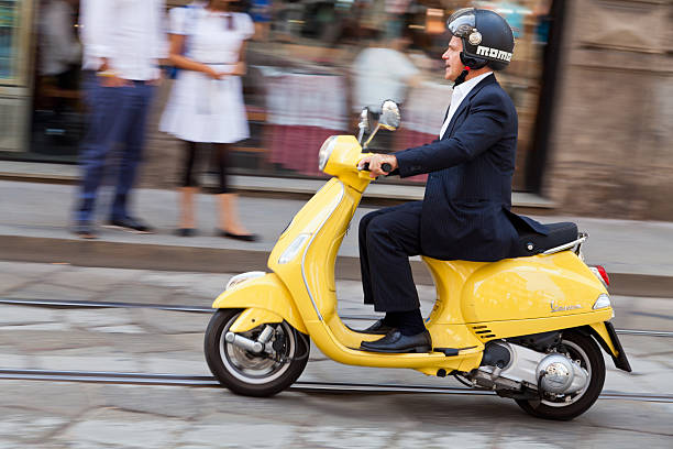 man riding his scooter through the streets of milan stock photo