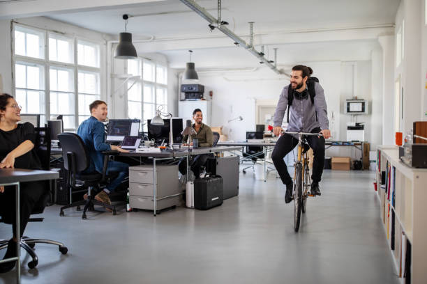 Man riding home on a bike from office stock photo