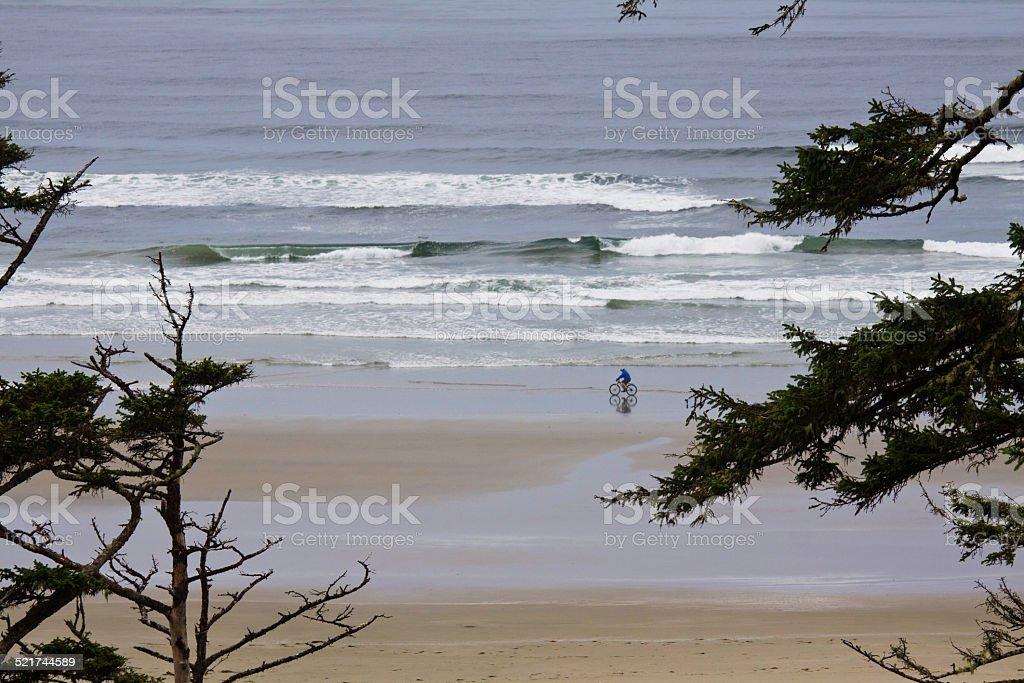 Man riding mountain bike along the surf on Long Beach stock photo