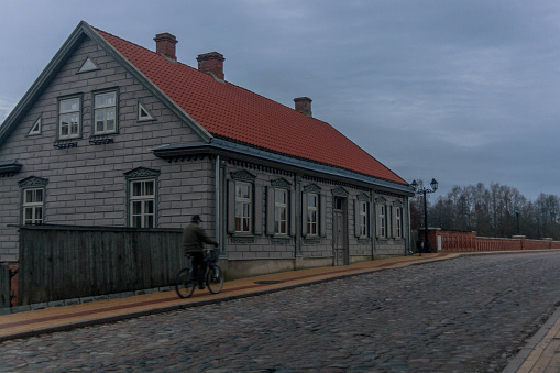 A man riding on a bike near renovated old house at the end of Kuldīga red brick bridge.