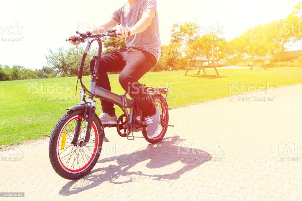Un hombre montado en una bicicleta eléctrica en un parque - foto de stock