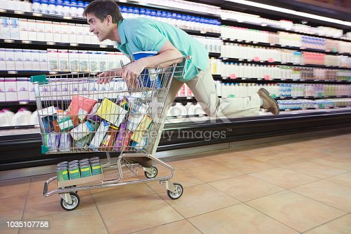 Man riding on shopping cart