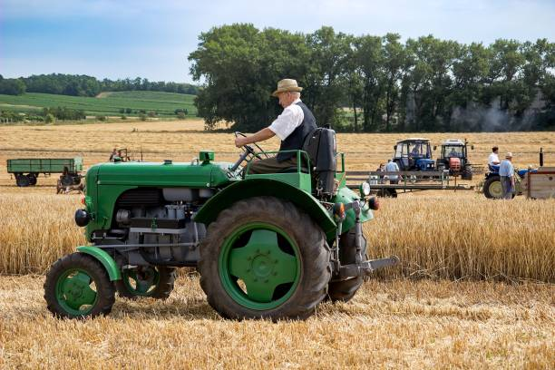 Man riding on the old model of tractor stock photo