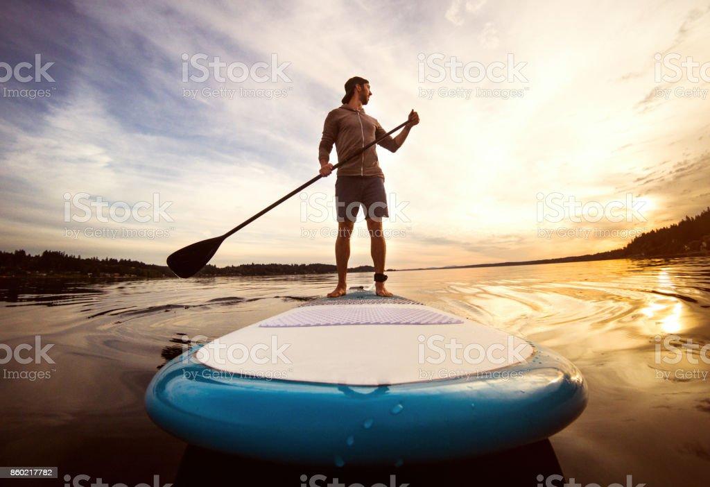 Man Riding Paddleboard on Puget Sound At Sunset stock photo
