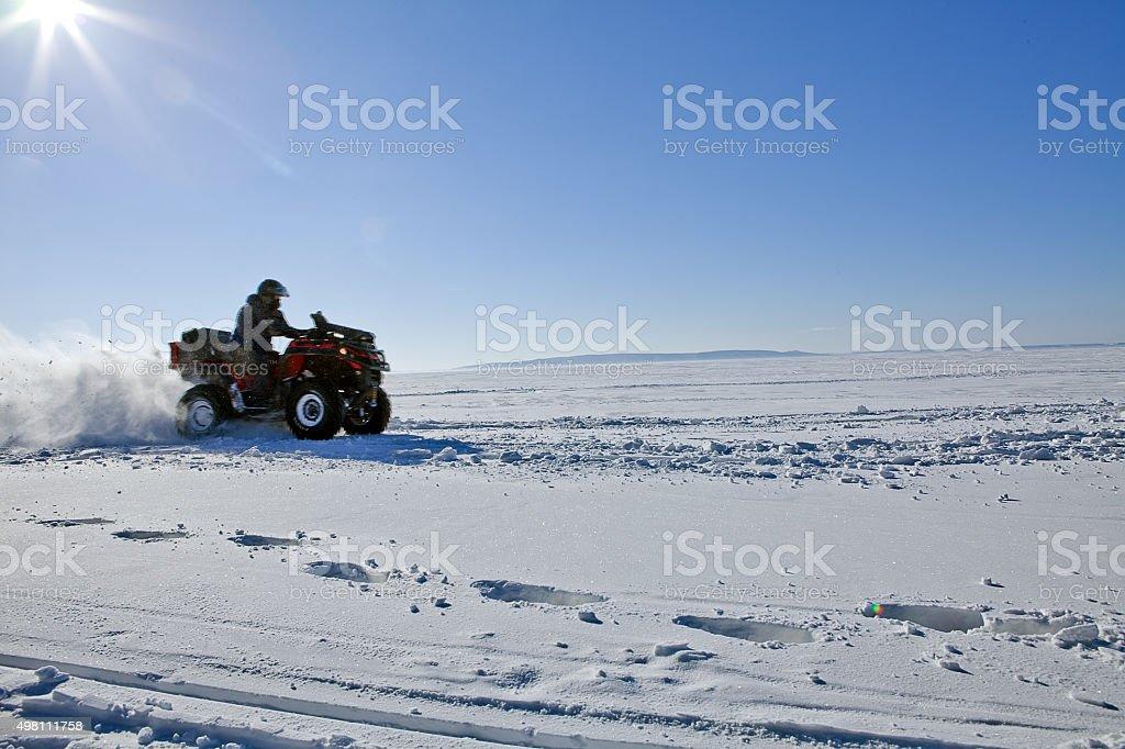 man riding quad bike on snowy winter field stock photo
