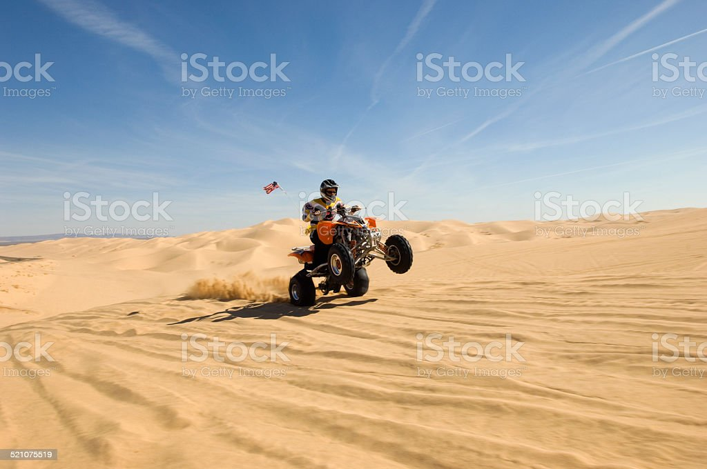 Young quad bike rider doing wheelie in desert