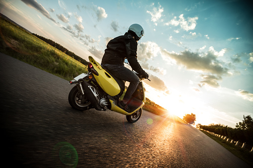 Man riding scooter on countryside during sunset.