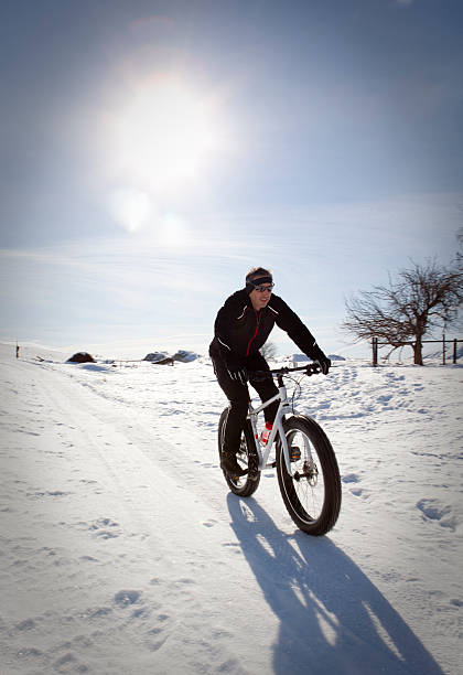 Man riding snowbike on a groomed trail. stock photo