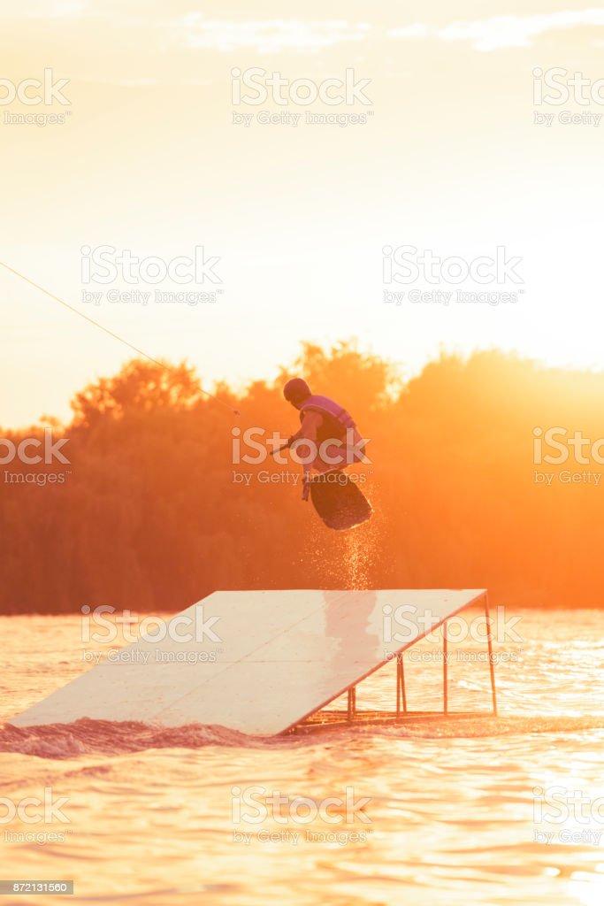 Man riding wakeboard performing midair stunts stock photo