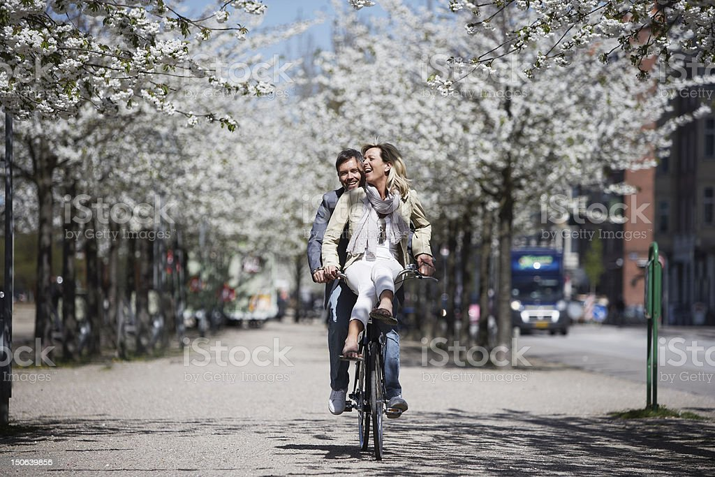 Man riding with girlfriend on bicycle stock photo