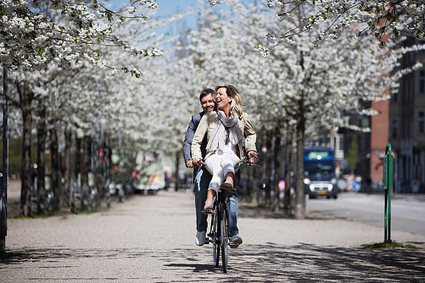 man riding with girlfriend on bicycle - denmark stock photos and pictures