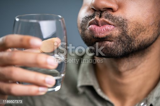 Close-up Of Man Rinsing And Gargling With Water In Glass