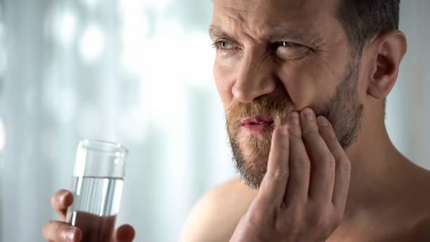 man spoeldouche tand met water, overgevoeligheid, scherpe tand pijn, gingivitis - dentine stockfoto's en -beelden