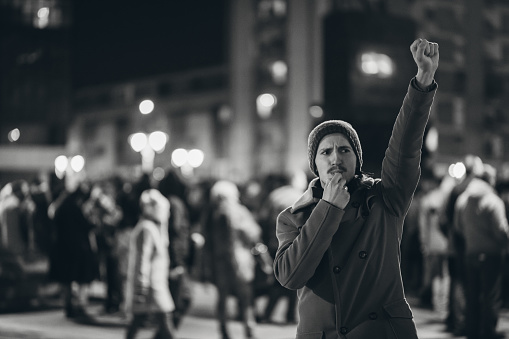 Brave young man rioting downtown. Whistling and raising fist. Black and white.